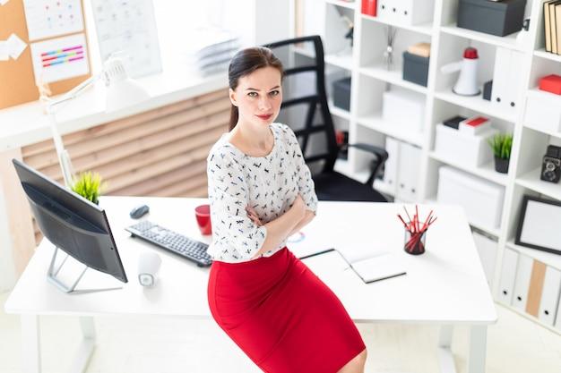 Una ragazza si sedette su un tavolo in ufficio.