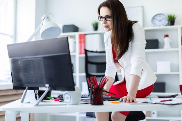 Una ragazza si sedette su una scrivania in ufficio e lavora con documenti e un computer.