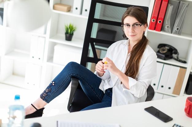 Una ragazza si siede a un tavolo in ufficio, getta il piede sul bracciolo e tiene un pennarello giallo