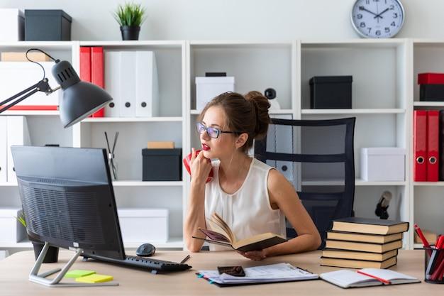 Una ragazza si siede al tavolo di un computer e tiene in mano un libro aperto e una tazza rossa.