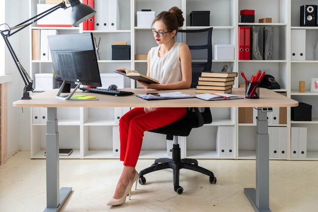 Una ragazza si siede al tavolo di un computer e tiene in mano un libro aperto.