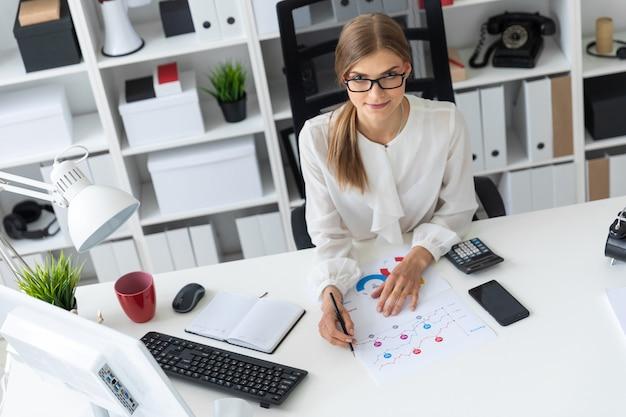 Una ragazza si siede alla scrivania di un computer in ufficio e tiene una matita in mano.