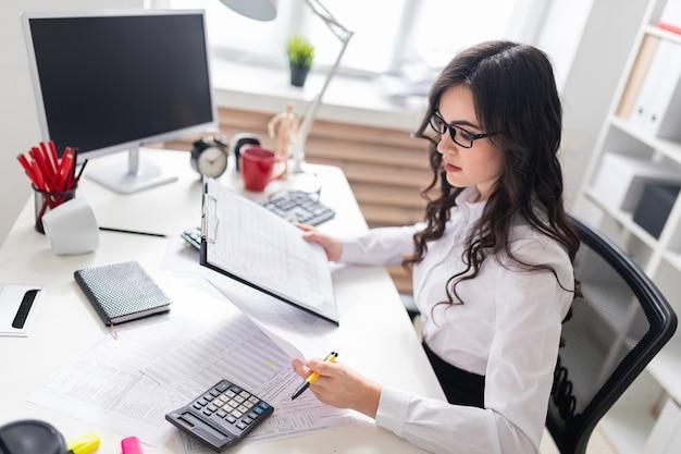 Una ragazza si siede alla scrivania e controlla i documenti.