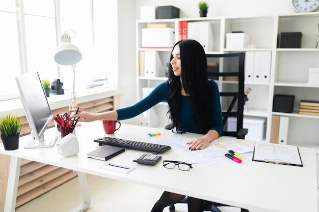 Una ragazza si siede in ufficio a un tavolo e betulle da un vaso a matita.