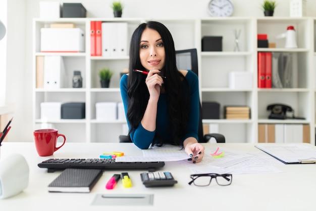 Una ragazza si siede in ufficio al tavolo, tiene una penna in mano e compila i documenti
