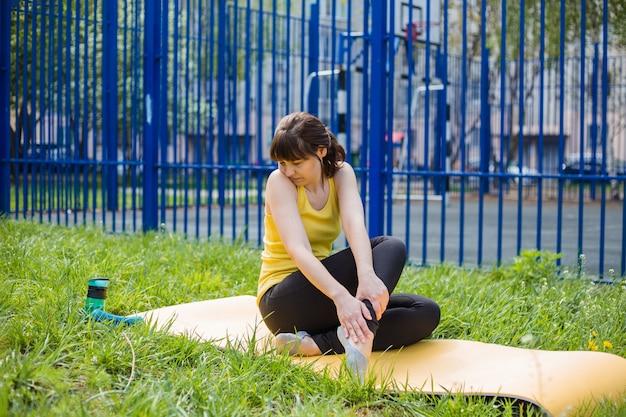 Una ragazza si siede su una stuoia di fitness e fa una smorfia per il dolore alla gamba. dolore alle gambe, malattie delle gambe.