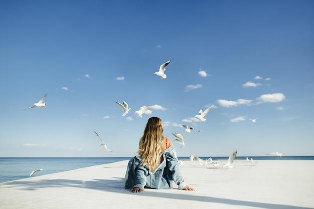 Una ragazza si siede sull'ormeggio e osserva i gabbiani