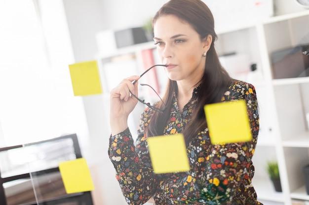 Una ragazza si trova in ufficio vicino a una tavola trasparente con adesivi.