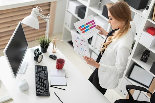 Una ragazza si trova nell'ufficio vicino al tavolo e tiene in mano documenti con incisioni e diagrammi.