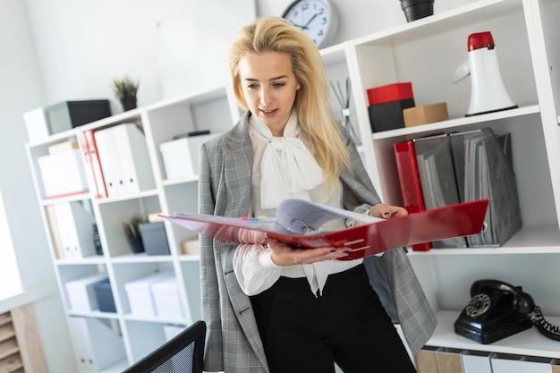Una ragazza si trova vicino a un rack in ufficio e scorre una cartella con i documenti.