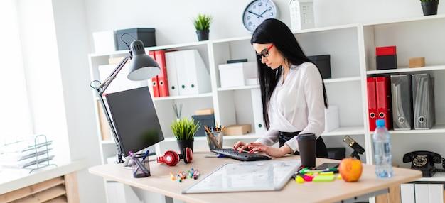 Una ragazza si trova vicino a un tavolo e stampa sulla tastiera prima che la ragazza sia una lavagna magnetica e dei pennarelli