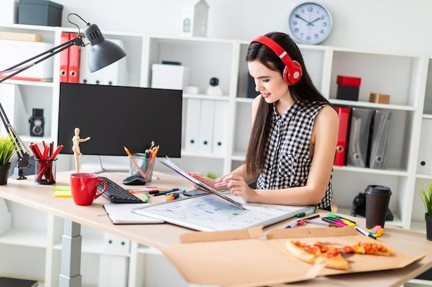 Una ragazza si trova vicino a un tavolo e tiene in mano un pennarello e dei fogli.
