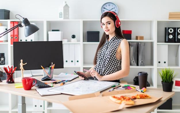 Una ragazza si trova vicino a un tavolo e tiene in mano un pennarello e un telefono.