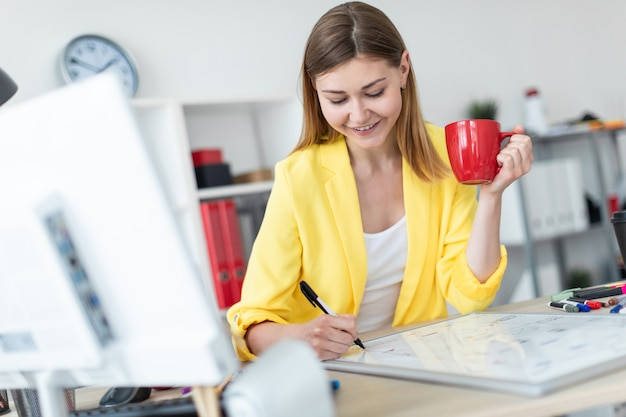 Una ragazza si trova vicino a un tavolo e tiene in mano una tazza rossa e un pennarello. davanti alla ragazza sul tavolo c'è una lavagna magnetica