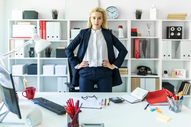 Una ragazza si trova vicino a un tavolo in ufficio, con le mani sui fianchi.