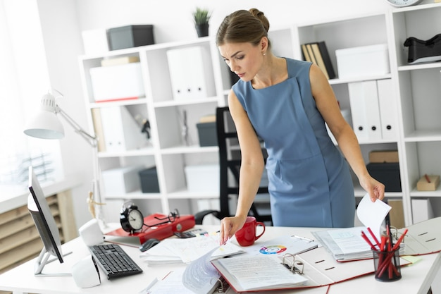Una ragazza si trova vicino a un tavolo in ufficio e scorre i documenti.