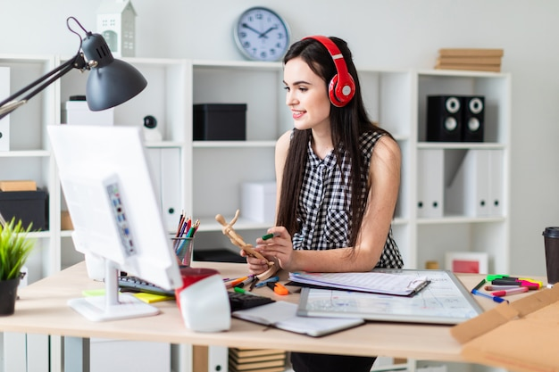 Una ragazza si trova vicino a un tavolo, tiene in mano una figura umana di legno e un pennarello verde e guarda il monitor. davanti alla ragazza sul tavolo c'è una lavagna magnetica.