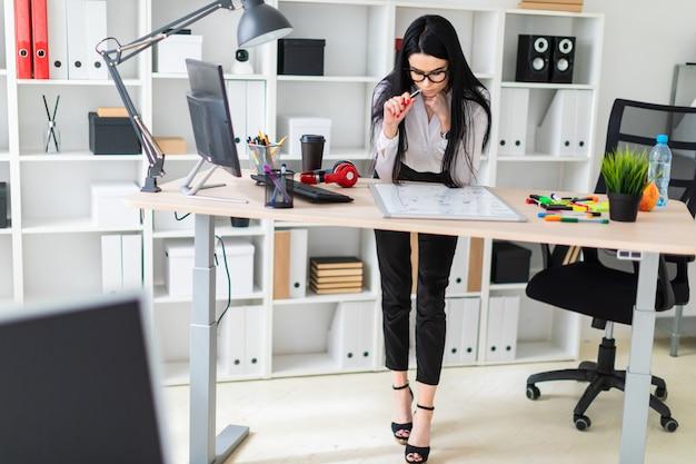 Una ragazza si trova vicino a una scrivania del computer e disegna un pennarello su una lavagna magnetica.