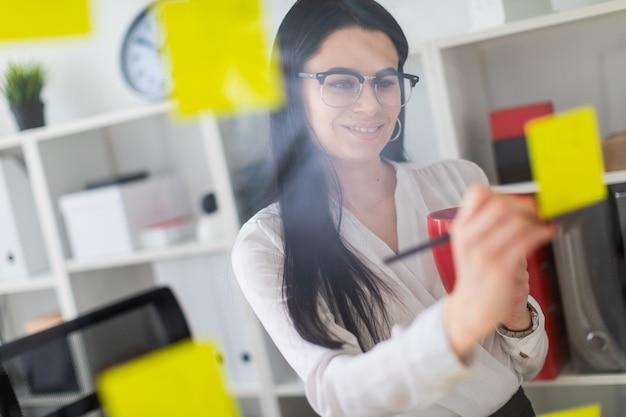Una ragazza si trova vicino al tabellone con adesivi e tiene in mano una tazza rossa e una matita.