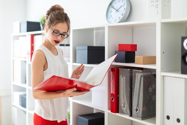 Una ragazza si trova vicino allo scaffale e tiene in mano una cartella rossa.