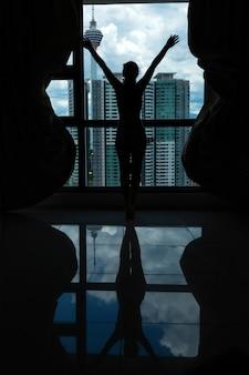 Una ragazza snella guarda la città da una grande finestra. piano alto.