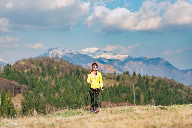 Una ragazza solitaria durante un trekking in montagna in primavera