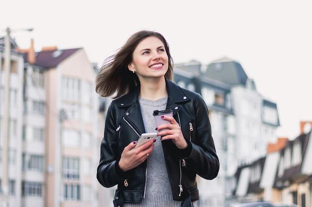 Una ragazza sorride e cammina per la città con un telefono cellulare e una tazza di caffè