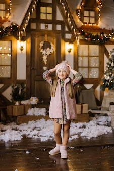 Una ragazza sorridente di sei anni in un cappello rosa e un gilet di pelliccia tiene le mani sulla testa, felice e gioisce nel nuovo anno e celebra il natale vicino a una bella casa di neve