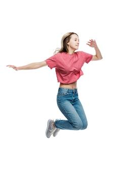 Una ragazza sorridente in jeans e una maglietta rossa sta saltando. positivo e felice. orecchio su un muro bianco. a tutta altezza. verticale.