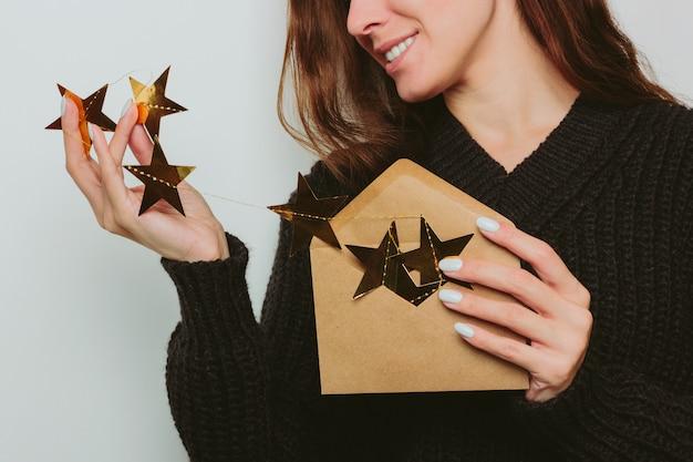 Una ragazza sorridente in un maglione scuro tira fuori una ghirlanda di stelle d'oro da una busta artigianale. sfondo grigio