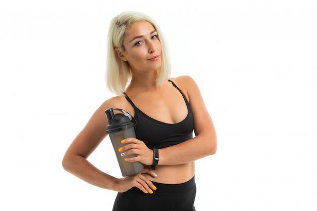Una ragazza sportiva con capelli biondi e manicure brillante detiene una bottiglia d'acqua sportiva.