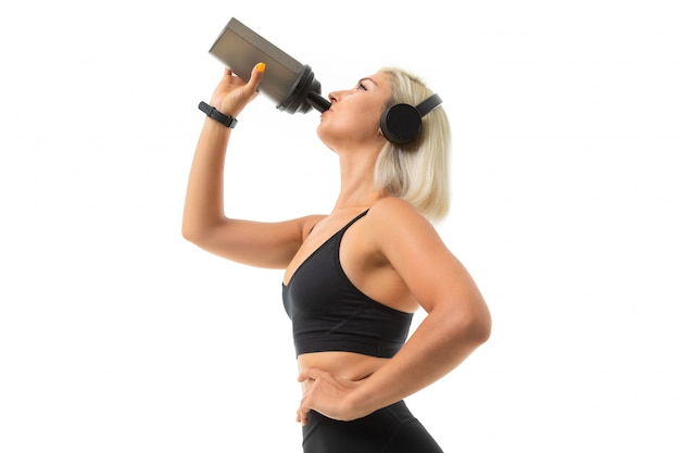 Una ragazza sportiva con capelli biondi e manicure brillante in cuffia, argomenti sportivi neri e leggings beve da una bottiglia d'acqua per lo sport.