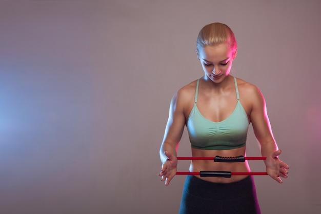Una ragazza sportiva detiene un espansore per il fitness, i muscoli sono tesi. fitness, sport, allenamento, persone e stile di vita