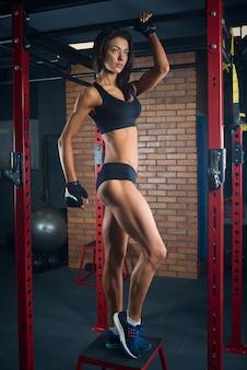 Una ragazza sportiva in un top corto nero e pantaloncini è in posa su una cella di metallo aggrappata a una barra orizzontale in una palestra.