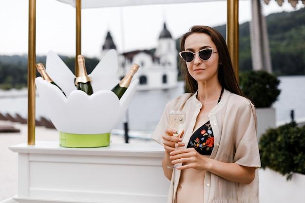 Una ragazza sta con un bicchiere di champagne sulla spiaggia
