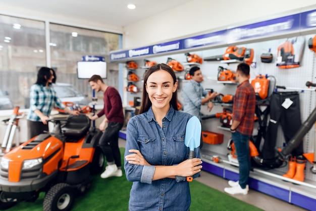 Una ragazza sta posando con una pala nel negozio.