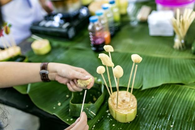 Una ragazza sta preparando i dolci. piano d'appoggio con foglia di banana