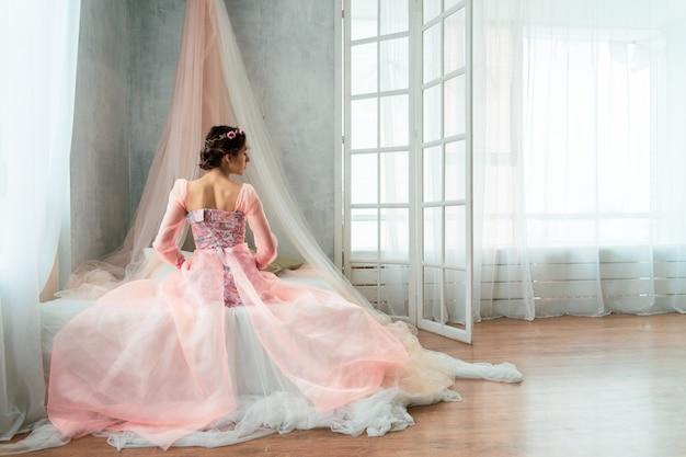 Una ragazza tenera nell'immagine di una principessa in un abito rosa con una corona in testa si siede sul letto con le spalle allo spettatore.
