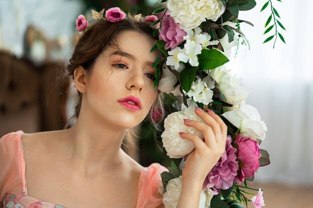 Una ragazza tenera nell'immagine di una principessa in un abito rosa con una corona in testa siede su un'altalena con fiori.