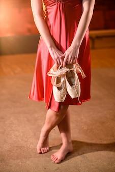 Una ragazza tiene le scarpe tra le mani