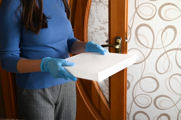 Una ragazza trasporta con cura un pacco da un negozio online cinese. usa guanti protettivi, poiché ha paura di essere infettata dal coronavirus