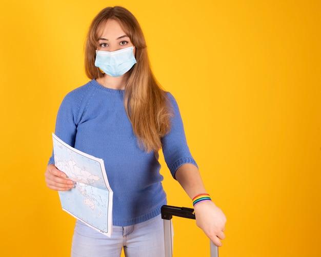 Una ragazza turistica con una mascherina medica, con una valigia, con un passaporto e biglietti aerei e una mappa, il tuo volo è stato cancellato da covid-19