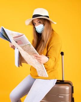 Una ragazza turistica in maschera medica, con valigia, cappello che consulta una mappa, voli cancellati da covid-19