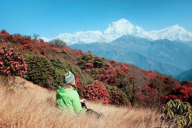 Una ragazza turistica in un luminoso cappello nepalese si siede sullo sfondo dell'himalaya innevato e rododendri in fiore. bella vista degli alberi di rododendro e delle montagne di fioritura della neve, nepal