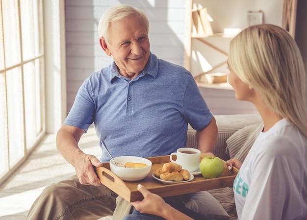 Una ragazza volontaria sta dando da mangiare al vecchio