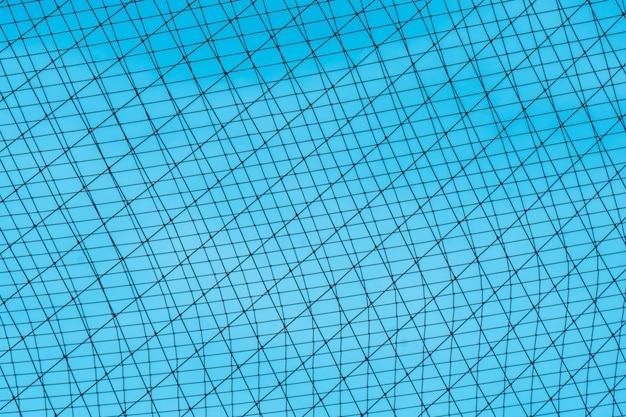 Una rete di corda nera si stendeva sullo sfondo, dietro il cielo azzurro.