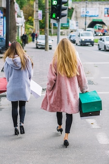Una retrovisione di due giovani donne bionde che tengono i sacchetti della spesa a disposizione che camminano sulla via