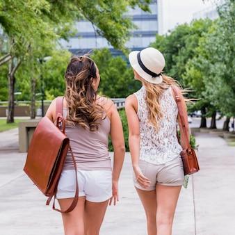 Una retrovisione di due giovani turisti femminili che camminano sulla via