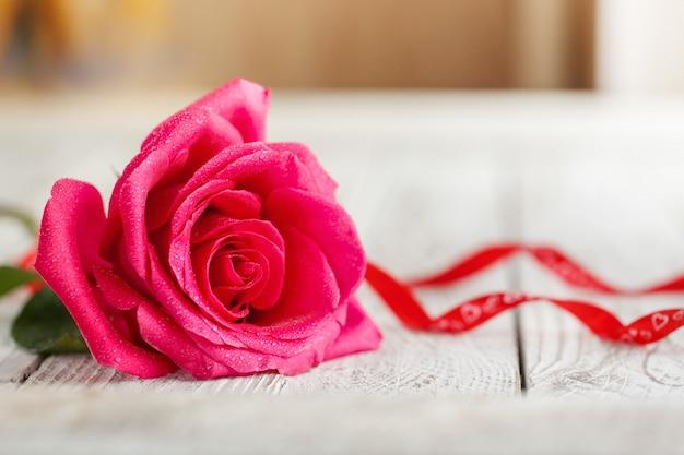 Una rosa rosa sul tavolo bianco
