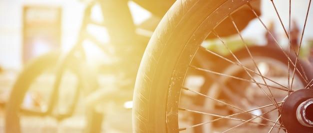 Una ruota di bicicletta bmx sullo sfondo di una strada sfocata con ciclisti. concetto di sport estremi